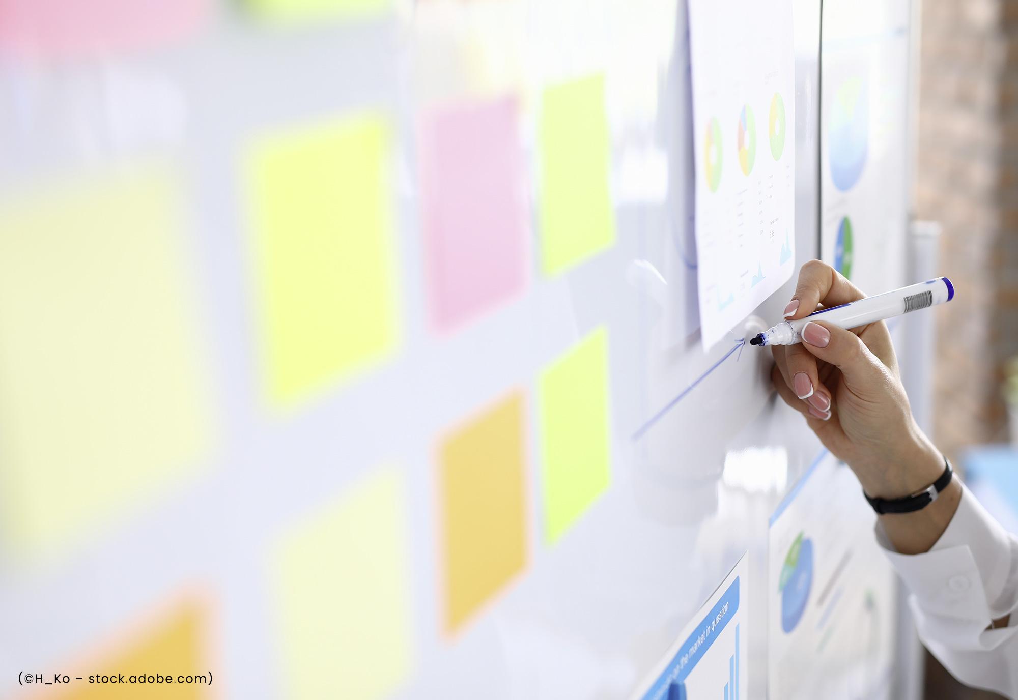 Frau zeichnet an weißem Board einen Belegungsplan